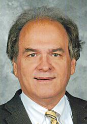 Professional headshot of older smiling man wearing white buttondow, yellow striped tie and blazer.