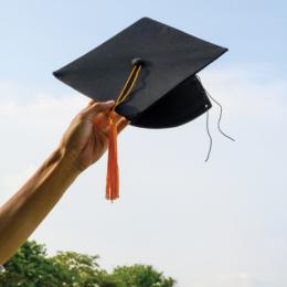 A hand holding a graduation cap