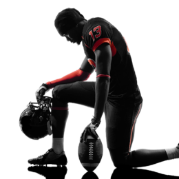 Silhouette of a black football player kneeling with head bowed.