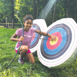 A photo of a young black girl infront of a shooting target in a field. She is holding a bow and arrow and showing off a bulls eye.