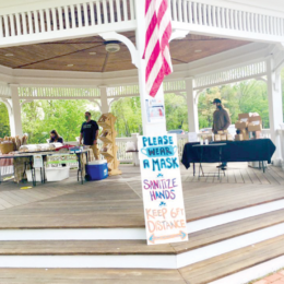 Photo of two farmers market vendor tables inside a gazebo. A sign in the forefront that reads, please wear a mask, sanitize hands, keep your distance