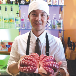 Photo of chef Eddie Saktanaset, a young Thai man wearing white buttondown, black tie, black apron and white chef's hat, holding a pink octopus, bar with wall of bottles behind him.