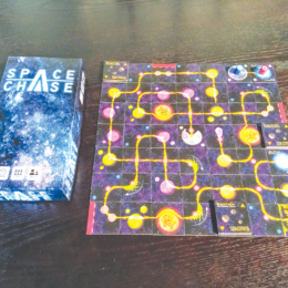 Photo of the board game Space Chase. A box and game board with galaxy theme and glowing graphics.