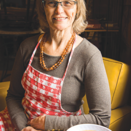 Photo of middle aged woman with glasses and long hair, wearing a gingham apron and sitting next to a table with a bowl of broth.