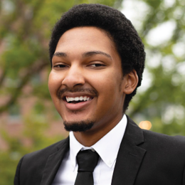 A young, attractive smiling black man in his 20's, with natural hair, a goatee, wearing a black suit and tie.