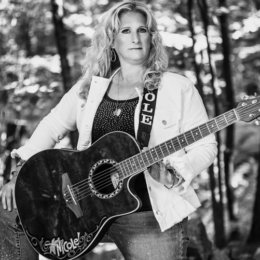 black and white photo of light haired woman in glittery black shirt and white denum jacket, jeans, holding an acoustic guitar.