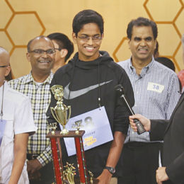Still from the documentary Spelling the dream, of a group of young Indian contestants and their families stand casually in front of large trophies.