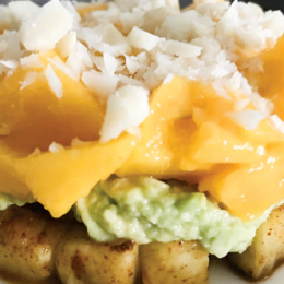 Stack of tropical fruit, including pineapple, mashed avacado, mango and crushed hazelnuts.