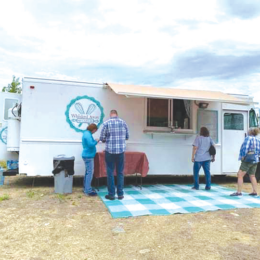 Photo of a white food truck, a small group of people milling about in front while they wait for food.