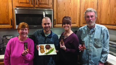four people standing in kitchen