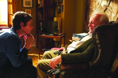 Woman speaks to old man in film scene