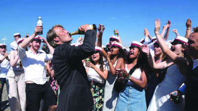 man drinking in crowd in movie scene