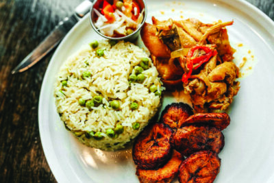Braised chicken with rice and peas, fried plantains, and pikliz.