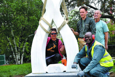 Four people standing around sculpture