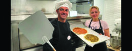 2 chefs holding pizzas