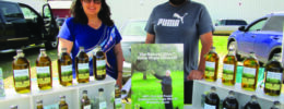 two people standing in farmers market tent behind product display