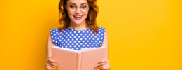 Photo of lady in blue dress holding an open book