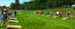 green field with tree in background, lines of people playing cornhole