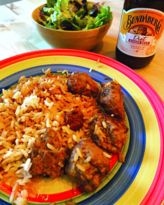 plate with pork meatballs and rice, bowl of green salad and a bottle of beer