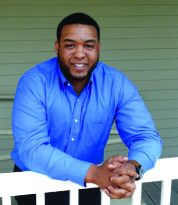 black man in blue shirt leaning on white railing