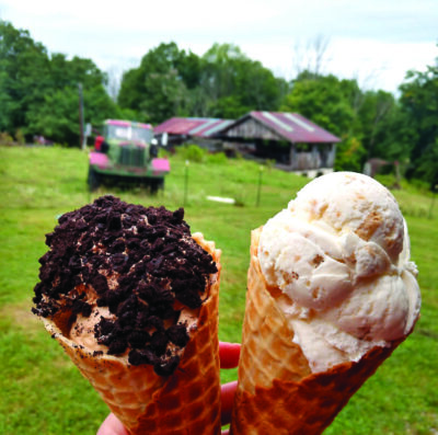 Hand holding up two ice cream cones in front of farm field, truck and barn in background