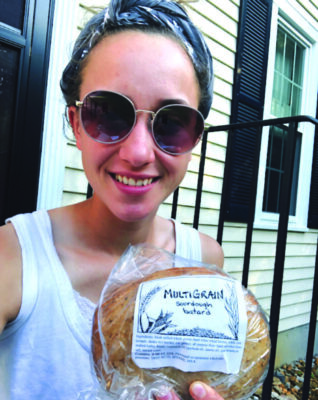 wpman wearing sunglasses in front of house, holding loaf of bread
