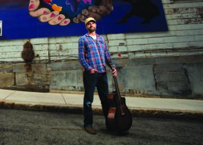 man standing in empty street holding guitar