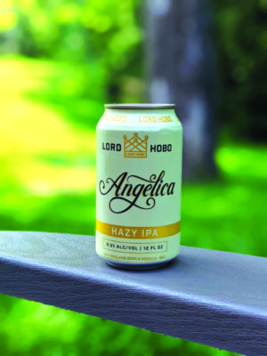 can of beer on wooden railing in front of blurry backyard