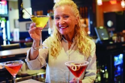 smiling older woman standing behind bar and holding up martinis
