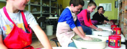 Line of children sitting at pottery wheels, in pottery studio, shaping clay
