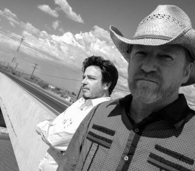 2 men standing in front of road, clouds in sky, one wears cowboy hat