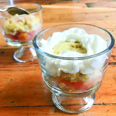 two glass dessert bowls filled with peaches, a biscuit and whipped cream on wooden table