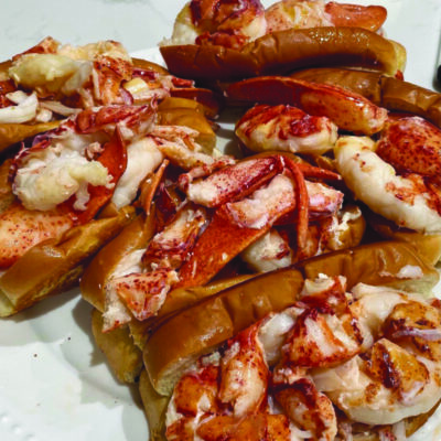 pile of lobster rolls on a white paper plate