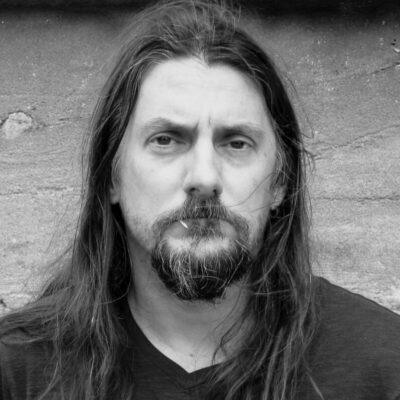 long haired man, with beard, looking straight ahead with serious expression