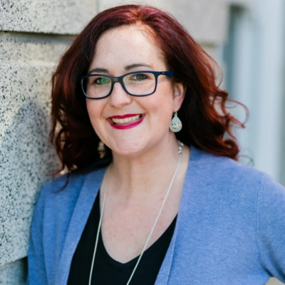 portrait of middle aged, red haired woman with glasses leaning against stone building