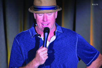 man in blue shirt and straw hat, speaking into microphone