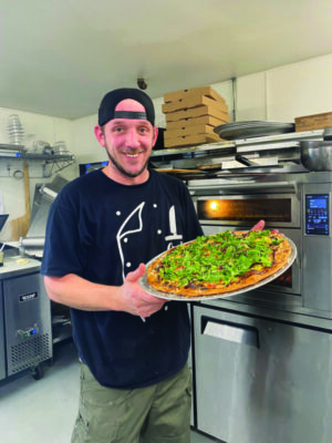 young man standing in restaurant kitchen holding up large pizza with green toppings