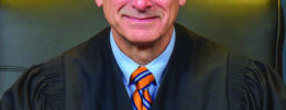 man in judges robe, sitting in chair, wearing blue shirt and orange striped tie