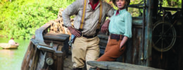 still from Jungle Cruise movie, man and woman posing on wooden boat, old fashioned clothing