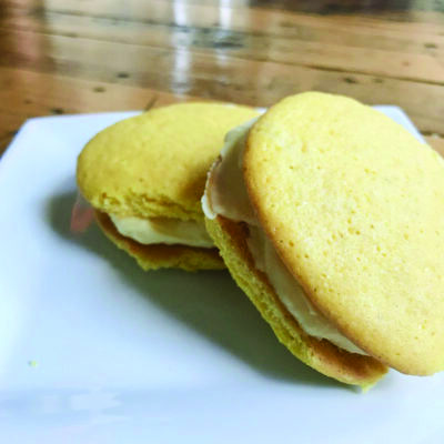 two lemon whoopie pies on white plate on wooden table