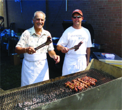 two men wearing aprons, standing behind large grill, holding up tongs with grilled meat