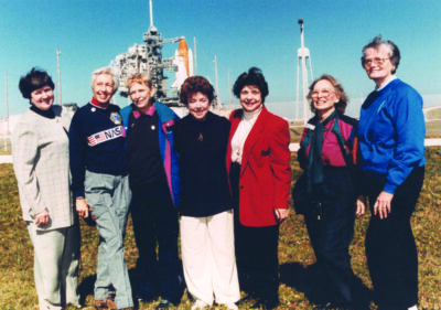 7 women standing in front of a space shuttle launch
