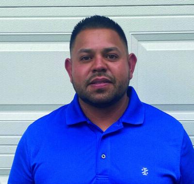 man with dark hair wearing blue polo shirt