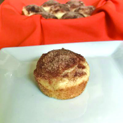 single muffin on white plate, in front of bowl of muffins