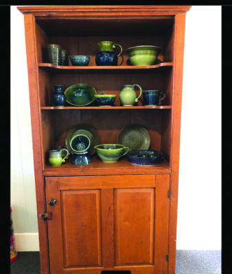 tall wooden cabinet with doors on bottom and shelves displaying pottery on top