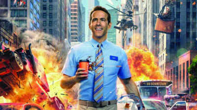 promotional still from movie, Free Guy, featuring man in blue button up shirt and striped tie, holding coffee, city exploding behind him