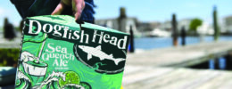 close up of man holding package of beer on a pier
