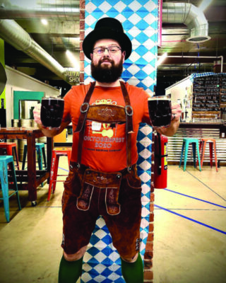 man dressed in traditional German clothes, holding two steins of beer, standing in modern restaurant decorated for Oktoberfest