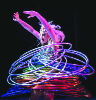 female performer doing a hula hoop act on dark background