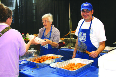 Elderly woman and middle aged man in blue aprons, serving food at long table